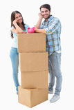 Happy young couple with moving boxes and piggy bank Stock Photo