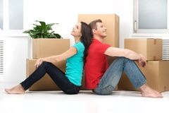 Happy young couple moving in new home. Man and women sitting on floor back to back Royalty Free Stock Images