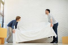 Happy Young Couple moving sofa. Or couch at their new home together. Moving house day stock image