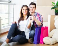 Happy young couple moving together in new apartment stock images