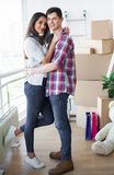 Happy young couple moving together in new apartment stock photography