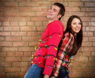 Happy young couple near brick wall with garland Stock Photo
