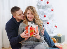 Happy young couple near Christmas tree with gift Stock Images