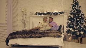 Happy young couple on New Year`s night lying on the sofa stock video