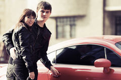 Happy young fashion couple next to sports car stock photography