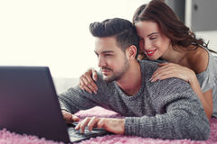Happy young couple online shopping at home Stock Image