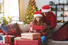 Happy young couple opening presents on Christmas morning stock photography