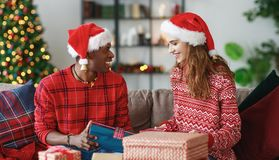 Happy couple opening presents on Christmas morning stock image
