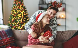 Happy young couple opening presents on Christmas morning stock photo