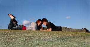 Happy young couple outdoors. A happy teenage couple lying on a hill on a sunny day Royalty Free Stock Image