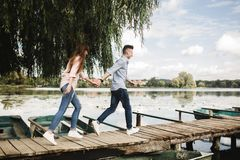 Happy young couple outdoors. young love couple running along a wooden bridge holding hands. royalty free stock image