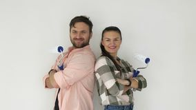 Happy young couple with paint rollers near white wall