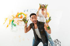 Happy young couple painting by hands and having fun Stock Photos