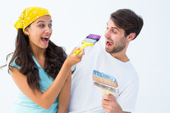 Happy young couple painting together and laughing Royalty Free Stock Photography