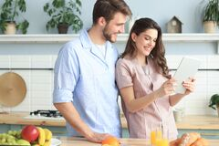 Happy young couple in pajamas watching online content in a didital tablet and smiling in kitchen at home