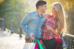 Happy young couple with a paper bag in the park. Royalty Free Stock Image
