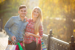 Happy young couple with a paper bag in the park. Royalty Free Stock Photography