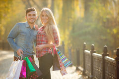 Happy young couple with a paper bag in the park. Royalty Free Stock Photo