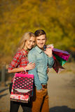 Happy young couple with a paper bag in the park. Royalty Free Stock Images
