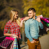 Happy young couple with a paper bag in the park. Stock Images