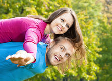 Happy young couple piggybacking, arms outstretched. Royalty Free Stock Photo