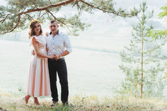 Happy young couple in a pine forest in summer stock photo