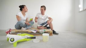 Happy Young Couple Planning Design Project for Their Apartment Sitting on Floor with Palette of Colors on White Wall stock video