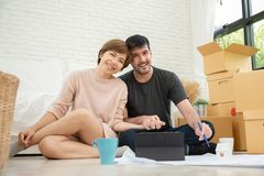 Happy young couple planning their new moving house. royalty free stock photography
