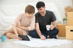 Happy young couple planning their new moving house. royalty free stock photo