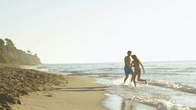 Happy young couple play near seashore in surf waves on sandy beach. Handsome man swirs with pretty girl stock footage