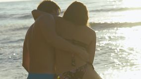Happy young couple play in surf waves on sandy beach. Handsome man swirls with pretty girl
