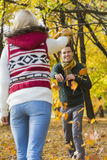 Happy young couple playing with autumn leaves in park Stock Image
