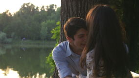 Happy young couple playing on a bench in the park and tickling. 4k stock video