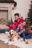Couple with dog at christmastime. Happy young couple playing with dog in antlers at christmastime royalty free stock photos