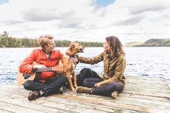 Happy young couple playing with dog on a dock Stock Photos