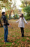 Happy young couple playing with leaves. At fall stock photography