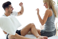 Happy young couple playing with pillows in the sofa. Stock Photo