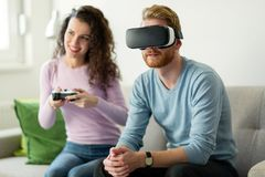 Happy young couple playing video games with virtual reality headsets Royalty Free Stock Photography