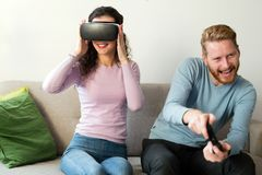 Happy young couple playing video games with virtual reality headsets Stock Photo