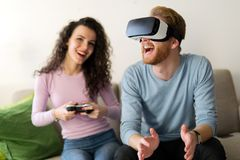 Happy young couple playing video games with virtual reality headsets Royalty Free Stock Photo