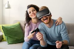 Happy young couple playing video games with virtual reality headsets stock images