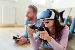 Happy young couple playing video games with virtual reality headsets Stock Photography