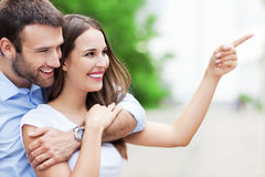 Happy young couple pointing finger Stock Image
