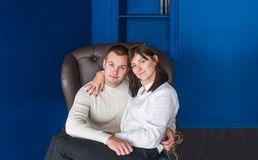 Happy young couple posing in chair on blue background royalty free stock image