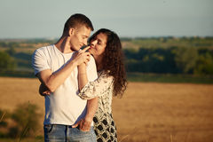 Happy young couple posing high on country outdoor over yellow field, romantic people concept, summer season Royalty Free Stock Image