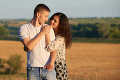 Happy young couple posing high on country outdoor over yellow field, romantic people concept, summer season Stock Photo