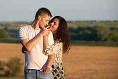 Happy young couple posing high on country outdoor over yellow field, romantic people concept, summer season Royalty Free Stock Photo