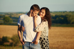 Happy young couple posing high on country outdoor over yellow field, romantic people concept, summer season Stock Photography