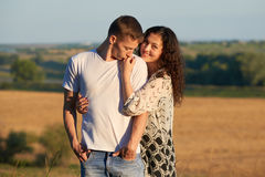 Happy young couple posing high on country outdoor over yellow field, romantic people concept, summer season Royalty Free Stock Images