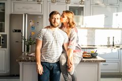 Happy Young Couple Posing at Home. Portrait of modern happy couple posing at home, wife kissing husband while sitting on kitchen counter stock images